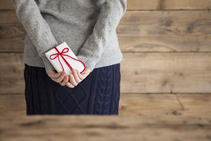 手にプレゼントを持つ女性