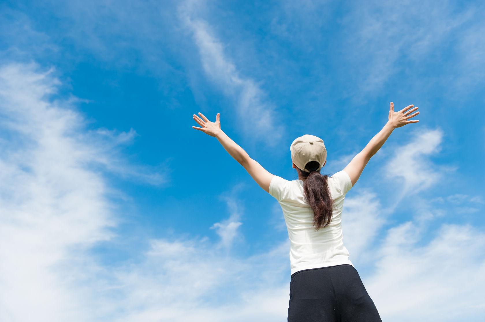 空に向かう女性
